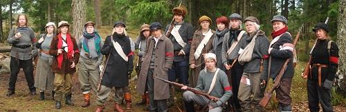 Kuvassa 15 yhteensopimattomiin vaatteisiin pukeutunutta housukaartinaista punanauhat olkavarressa aseiden kanssa.