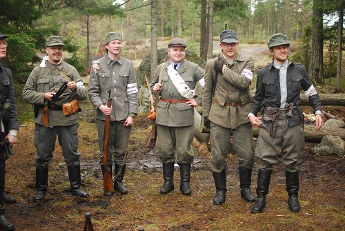 Kuvassa sekalaisiin uniformuihin pukeutuneet 5 sotilasta, hymyilevät kameran oikealla puolella tapahtuvalle asialle (mikä onkaan).