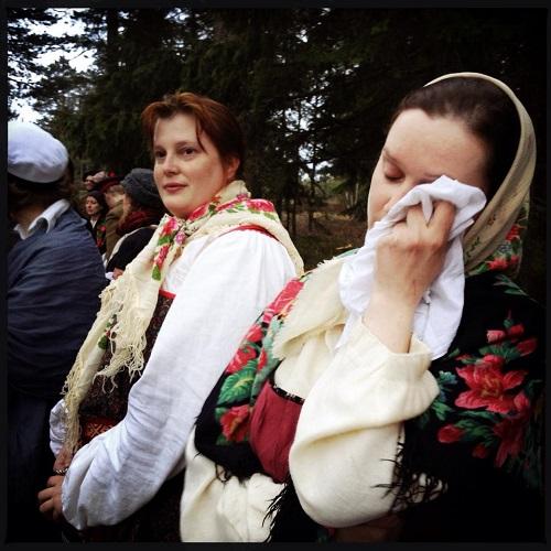 Karjalainen nainen itkee isoon nenäliinaan, vieressään toinen. Ovat pukeutuneet karjalaisittain kukkahuiveihin.