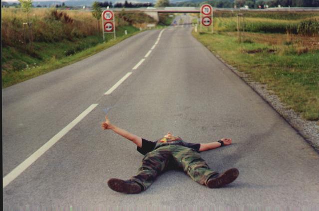 liftaaja makaa autotiellä peukku ojossa