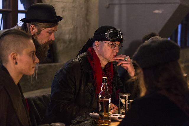 Palaveri, mies silmösuojusten, tiimalasin ja viskipullon kanssa.