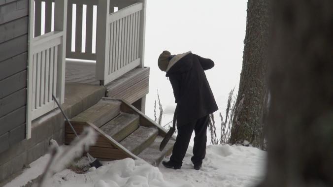 Kuvassa yhteisön asukas poistaa jäätä rappusista.
