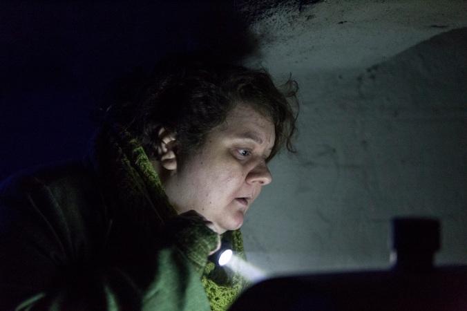Hahmo osoittaa jotain taskulampulla ja tuijottaa intensiivisesti.