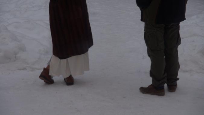 Kaksi ihmistä seisomassa lumihangessa, vyötäröstä alaspäin.