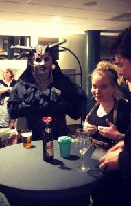 Kuvassa demoni ja MMasi Hannula pöydän äärellä pitelevät rinnuksiaan.