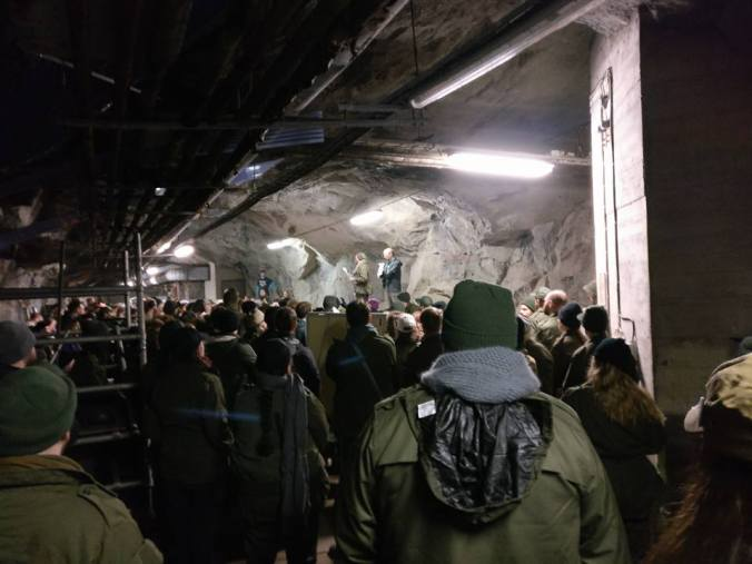 Ihmisiä bunkkerissa kuuntelemassa korokeella puhuvia henkilöitä, halogeenivaloa, armeijakuoseja ja värimaailmaa.