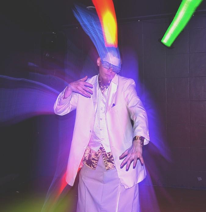 Tanssiva valkoiseen pukeutunut henkilö värivalojen loisteessa.