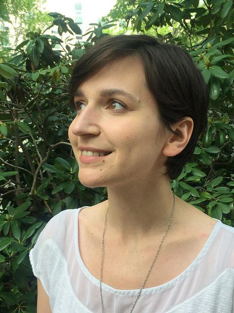Alex Roberts katsoo vasemmalle kiinanruusu taustallaan valkoisessa paidassa, hymyilee.