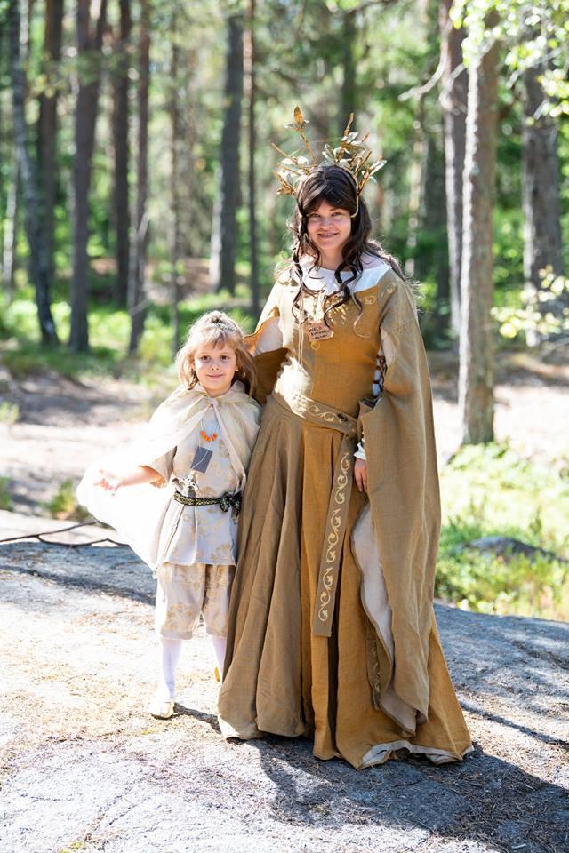Pienihaltiaprinssi haltiakuningattaren kanssa, vaatteissa kultaa ja helmiäistä.