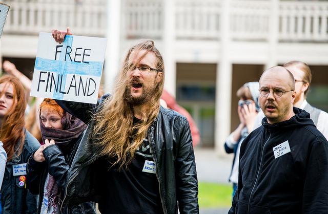 """mielenosoittaja pitelee """"free Finland"""" kylttiä ja huutaa, taustalla muita mielenosoittajia"""