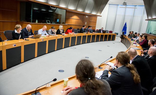 larppajat ja mepit istuvat kokoushuoneessa oikeassa Euroopan parlamentissa, EU:n lippu taka-alalla