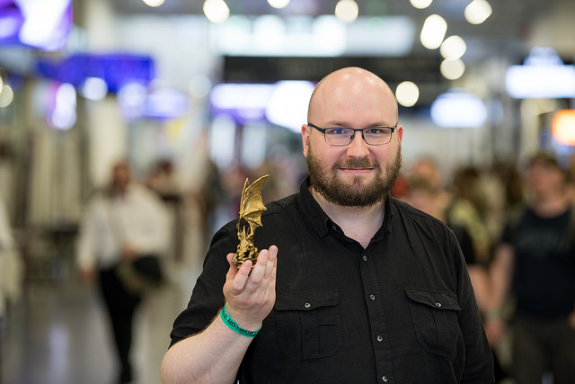 Juahna Pettersson Messukeskusksessa mustassa paidassa pitelee Kultainen lohikäärme patsasta ropecon ranneke ranteessaan