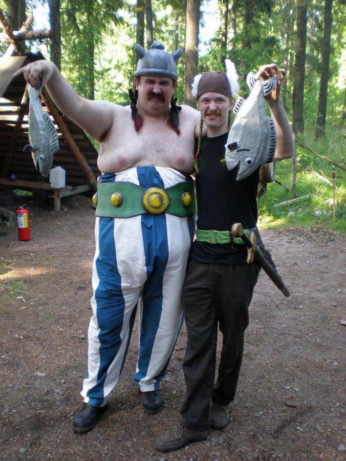 Asterix ja Obelix sarjakuvahahmoja elävöittävät miehet pitelevät tekokaloja ilmassa.