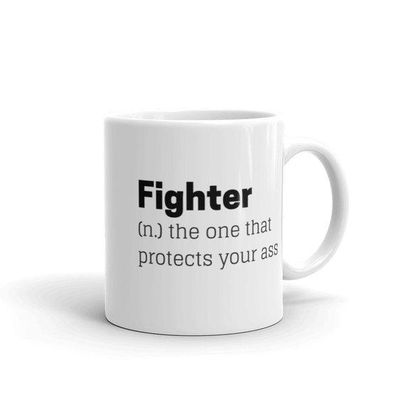 Kuvassa muki, jossa lukee Fighter (n) the one that protects your ass