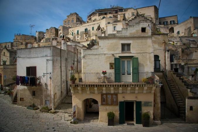 Kuvassa kohoava kaupunki auringonvalossa, talon terassilla roikkuu pyyhkeitä. Kaupunki näyttää hylätyltä mutta samalla pyykit kertovat asutuksesta.