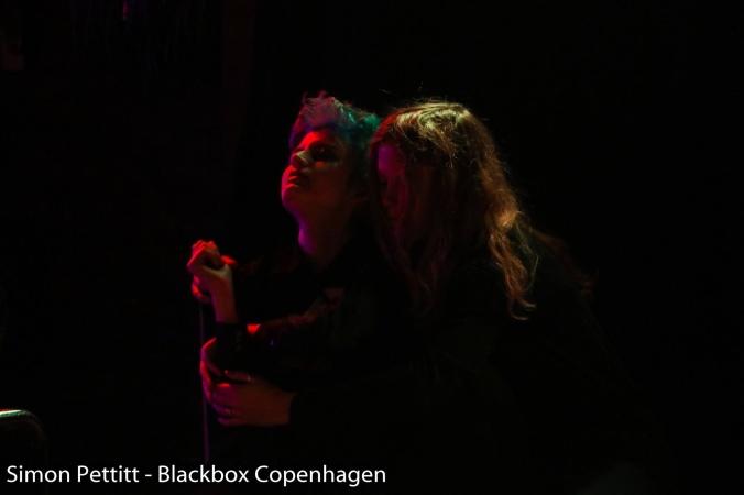 Kuvassa kaksi punaisen valon valaisemaa ihmistä syleilyssä mustassa ympäristössä.