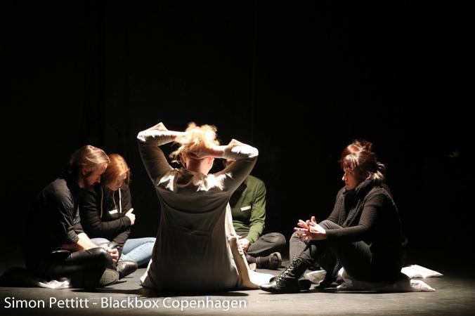 Kuvassa spottivalon valaisemat ihmiset istuvat ringissä lattialla.