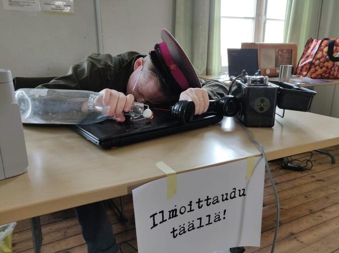 """Koppalakkipäinen pelinjohtaja makaa läppärin kannen päällä unessa. Pöydän päässä on lappu """"ilmoittaudu täällä!"""""""