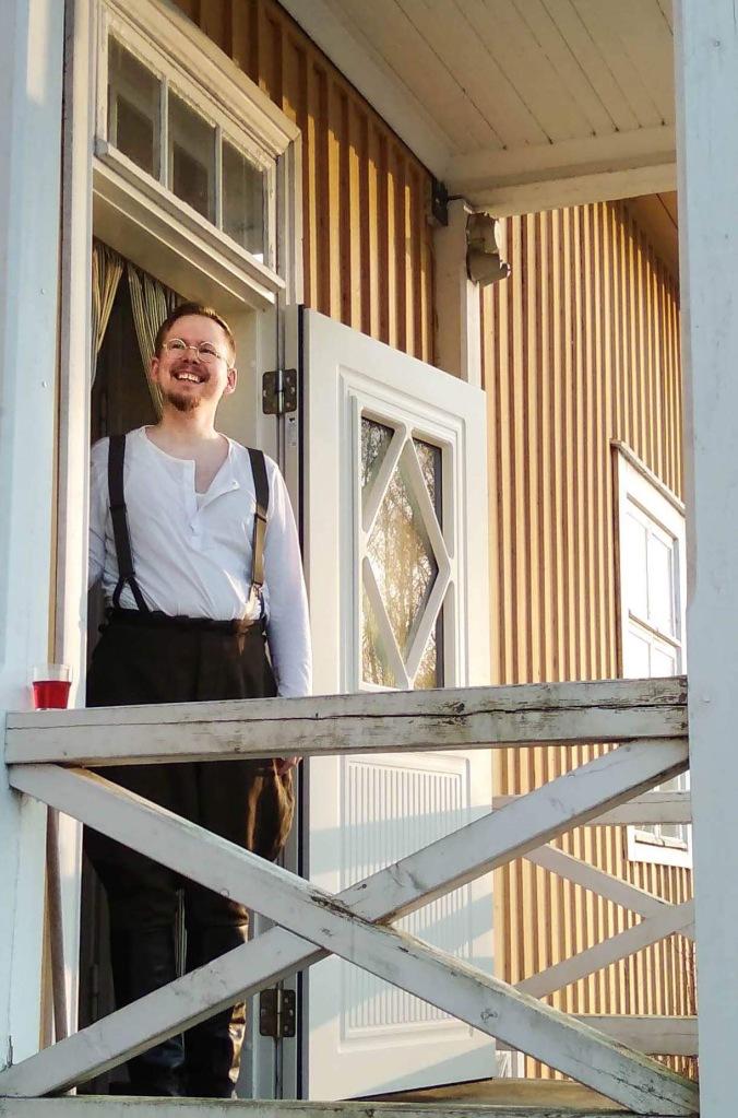 pelinjohtaja seisoo keltaisen puutalon ovella valkoisessa sarkapaidassa ja pussihousuissa