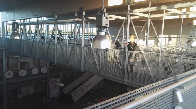 Kuvassa harmaita metallirakenteita, ihminen seisoo parvekehallin korkeuden mittana.