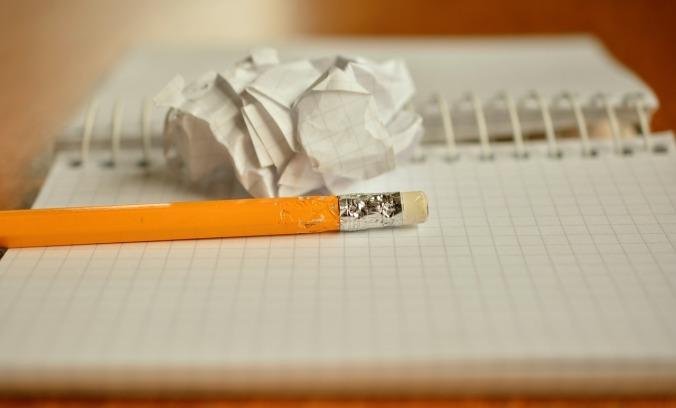 kuvassa ruutuvihko, rypistetty paperi ja päästä pureskeltu lyijykynä
