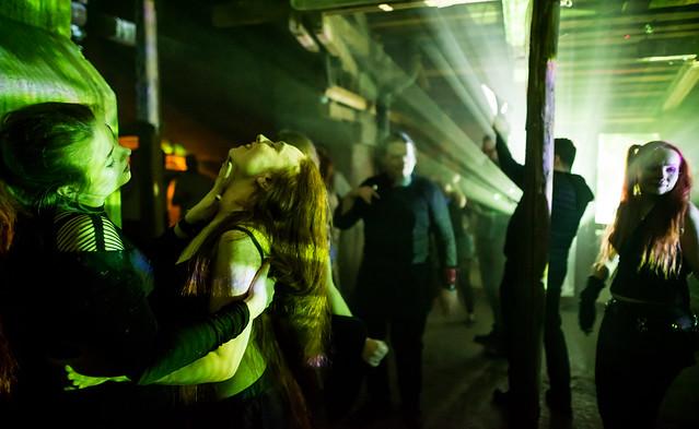Strobo-valojen loisteessa tanssijoita, etuallalla sensuellisti tanssija hivelee naisen kaulaa.