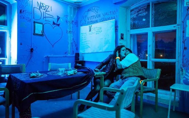 Sinisessä huoneessa jossa on graffitteja sienillä vampyyri puree naista kaulasta. He istuvat sohvalla.