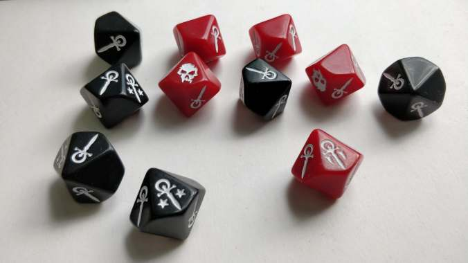kuvassa d10 noppia, mustia ja punaisia, joiss anumeroiden sijaan on erilaisia ankh-merkkejä ja pääkalloja