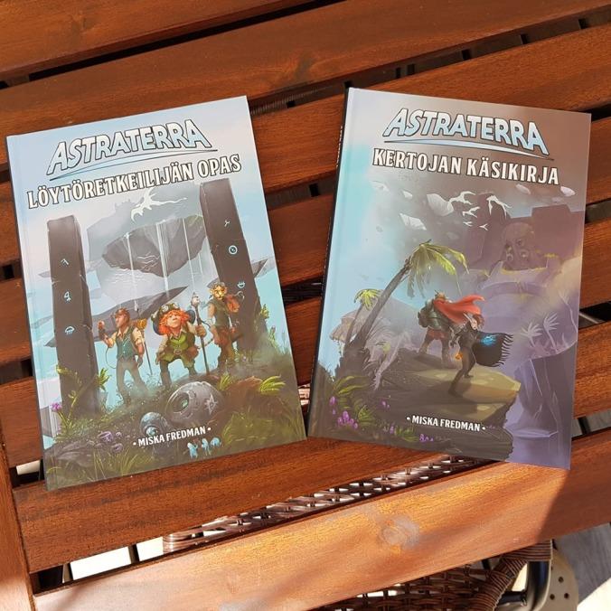 Kuvassa roolipelikirjat Astraterra löytöretkeilijän opas ja kertojan käsikirja