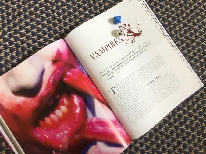 """Kuvassa kirjan aukeama, jossa vasemmalla puolella on verinen vampyyrin suu, oikealla kaksi noppaa kirjan päällä ja kirjan teksti """"Vampires"""""""