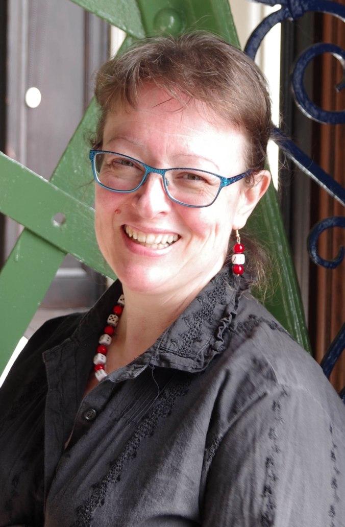 Kuvassa Lynne HArdy hymyilee, hänellä on ruskea tukka, sinisankaiset silmälasit, harmaa kauluspaita sekä puna-valkoiset korvakorut ja kaulakoru
