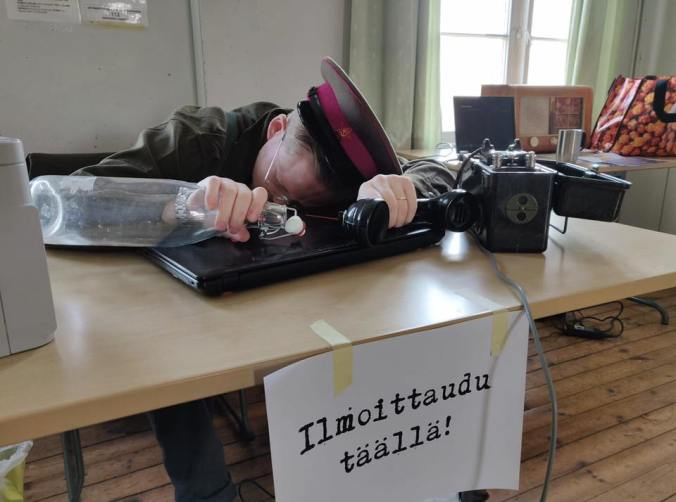 uniformuun pukeutunut pelinjohtaja makaa läppärin päällä pöydän ääressä lasipullo ja antiikkinen puhelin kädessää, pöydän reunassa lukee Ilmoittaudu täällä!