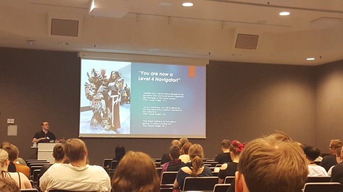 """kuvassa ihmisiä salissa katsomassa esitelmää. Powerpointissa seinällä lukee """"you are now a level 4 navigator"""""""