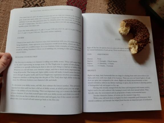 Kuvassa aukeama kirjasta, jossa karusti taitettua tekstiä ilman kuvia. Mittakaavan vuoksi donitsi. Sivut ovat n. A4-kokoa.