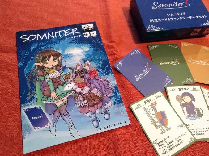 Kuvassa kirjava japanilainen sääntökirja, jonka kannessa kaksi fantasiahahmoa. Vieressä levitettynä taistelumekaniikassa ja hahmonluonnissa käytettäviä kortteja.