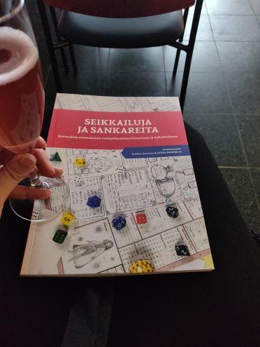 """Kuvassa lasillinen kuohujuomaa, sekä Särkijärven ja Stenrosin """"Seikkailuja ja sankareita""""-kirja."""