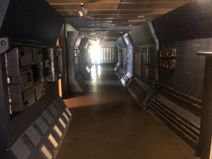 Kuvassa avaruusaluksen käytävä, seinämoduulit asennetuna paikoilleen, harmaata metallia, hohtavaa valoa.