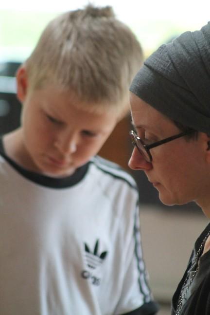 Kuvassa huivipäinen nainen opastaa nuorta poikaa jossain yhteisessä tehtävässä.