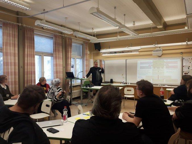 Kuvassa menossa luento, jossa luennoitsija näyttää kalvoja projektorista, osallistujat seuraavat pöytien ääressä istuen.