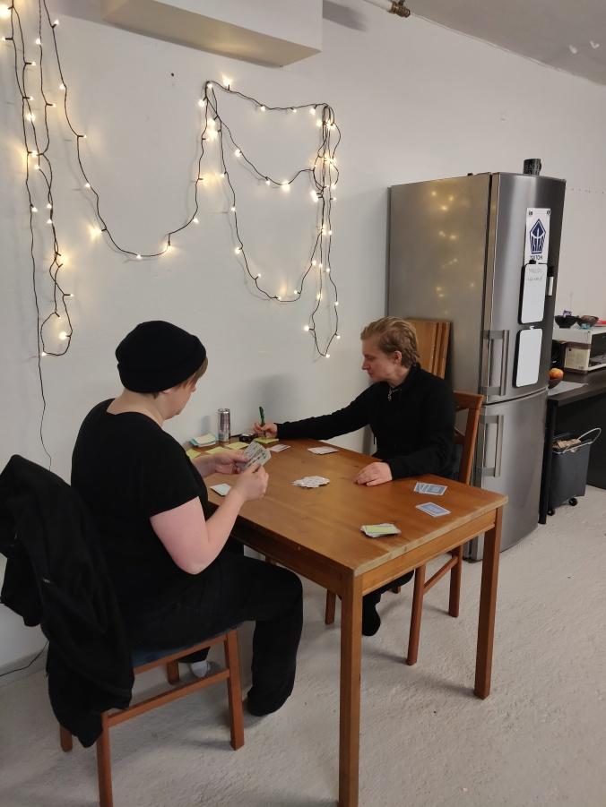 kaksi ihmistä tuolin pöydän ääressä pelaamassa korttia, taustalla pieni toimistokeittiö ja jouluvalot