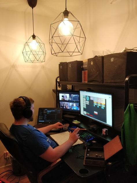 Elmeri istumassa etäpelin äärellä. Yhdessä näytössä chatti, toisessa videopuhelu ja kolmannessa virutaalinen roolipelipöytä.