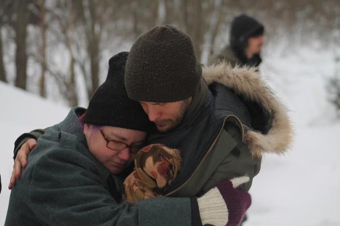 äiti ja isä halaavat rutistaen pientä vauvaa välissään, talvivaatteissaan hyisessä ulkoilmassa, lumen keskellä.