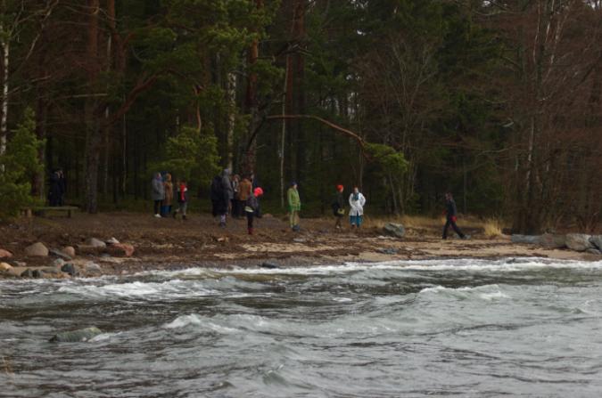 Kuvassa hahmoja meren rannalla syksyisen oloisessa tuulisessa säässä.