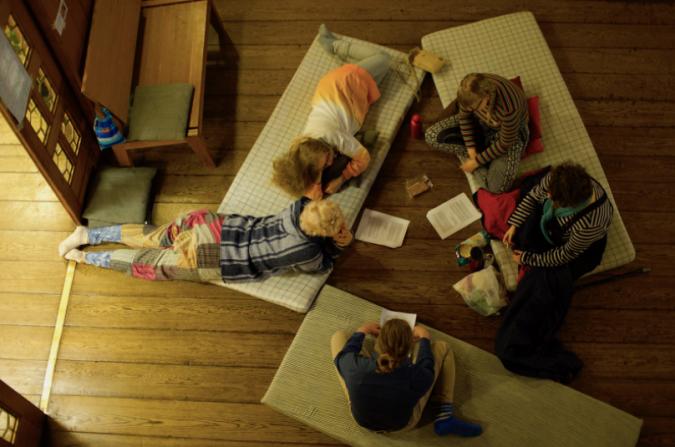 Kuvassa ihmiset istuvat lattialla patjojen päällä tekemässä tehtävää, joka ons elvästi annettu isoina paperinippuina joissa on paljon tekstiä.