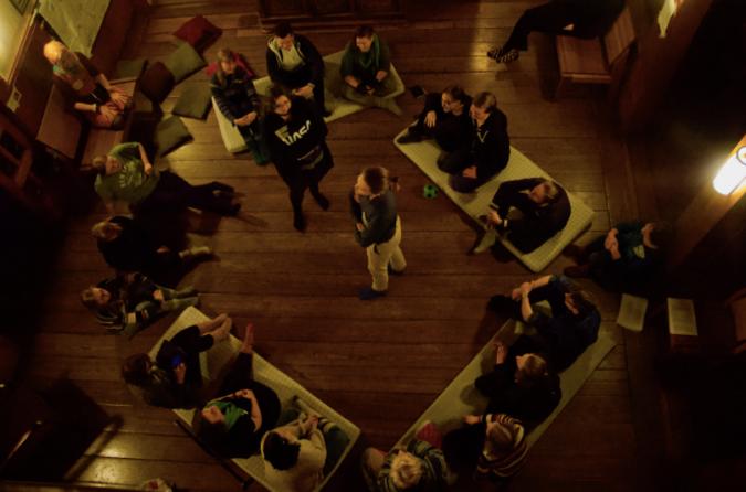 """Kuvassa leikitään leikkiä, jossa muut istuvat ympyrässä lattialla ja kaksi """"esittäjää"""" seisovat piirin keskellä."""