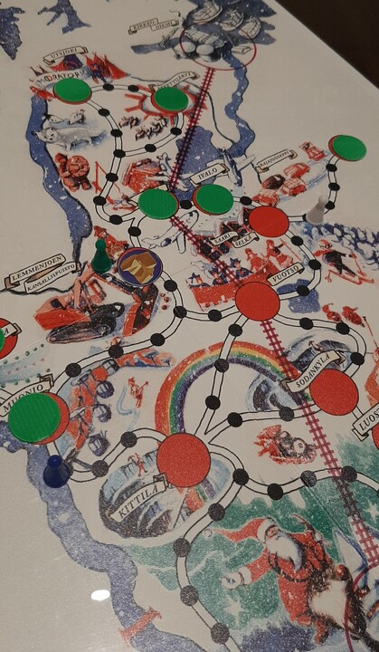 Kuvassa pelilauta ja afrikan tähti lautapelin tyylisiä nakkuloita.