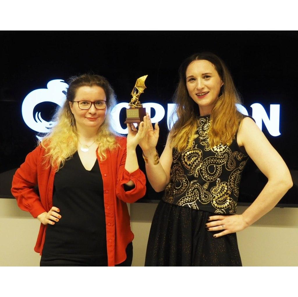 Kuvassa Laura Kalli ja Katri Lassila pitelevät kultainen lohikäärme patsasta. Takana Ropeconin logo.