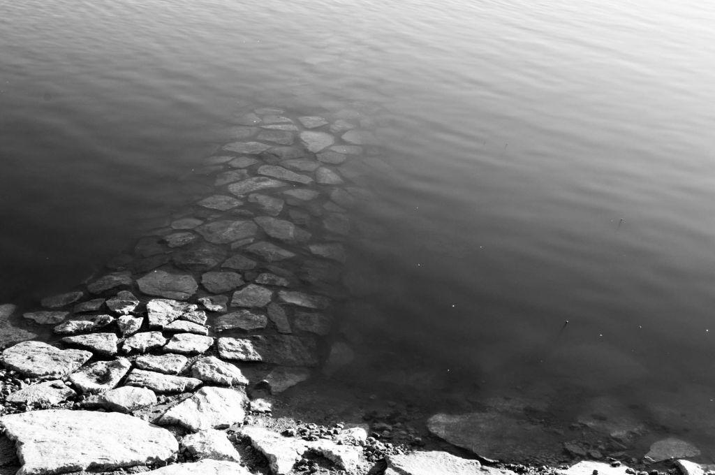 Rantakivetys muodostaa polun, joka johtaa veteen ja katoaa sinne.