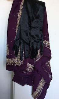 Kuvassa itämaisen näköisiä vaatteita roikkumassa naulassa, päällimmäisenä silkkiset mustat hanskat.