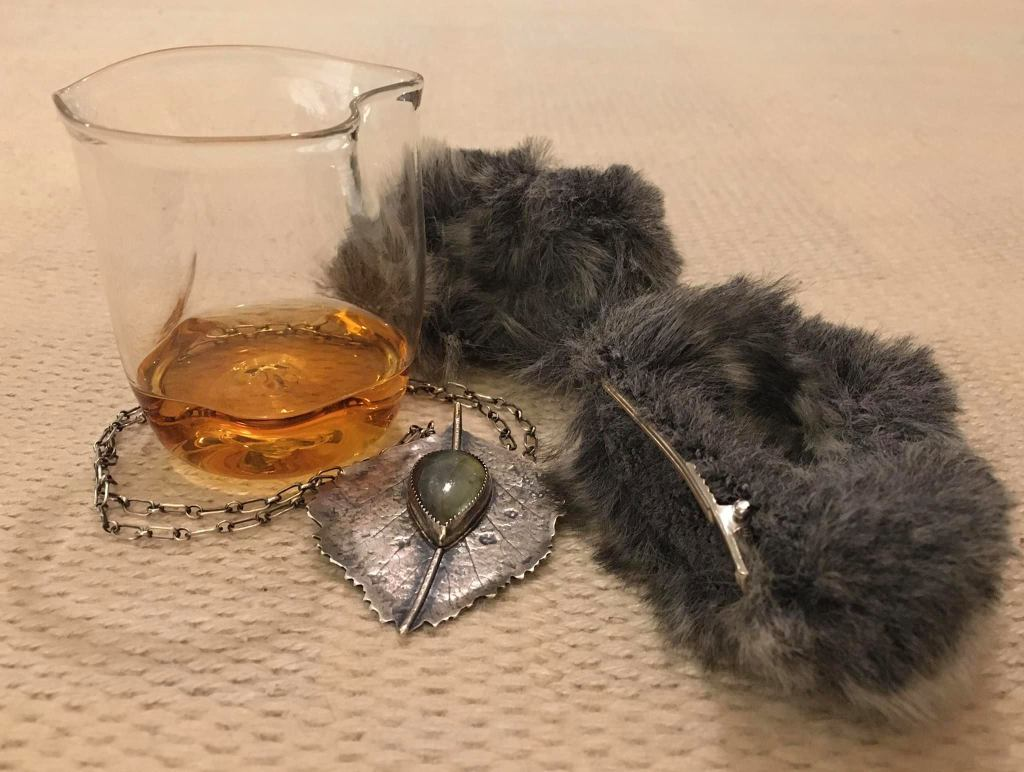 Kuvassa, harmaata turkista ja malja viskiltä näyttävää juomaa sekä hopeakoruja.